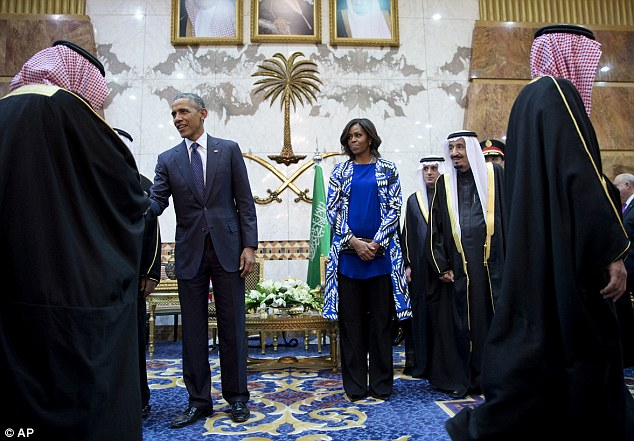 michelle obama stands behind the president