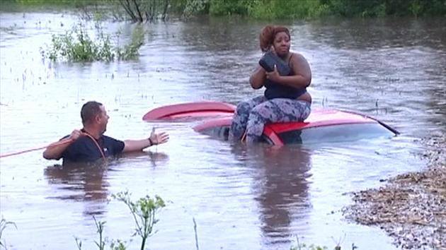 Woman Trapped On Top Of Her Car Being Rescued From Flood Can't Seem To Stop Talking On Her Cell Phone