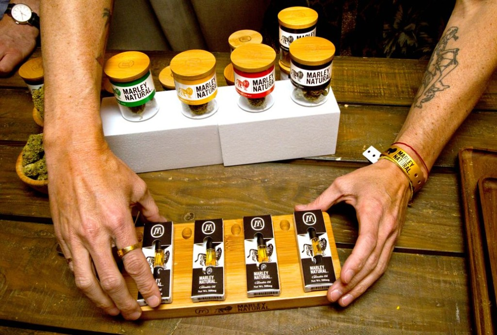 Sales Rep for Marley Natural lays out oils and vials of marijuana. Photo Credit: Steve Appleford