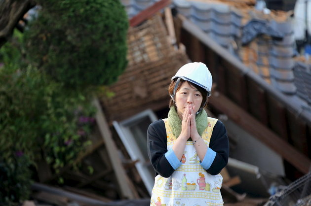 Woman in shock after homes were destroyed during the April 16, 2016 earthquake in southern Japan. Photo Credit: KYODO KYODO / REUTERS