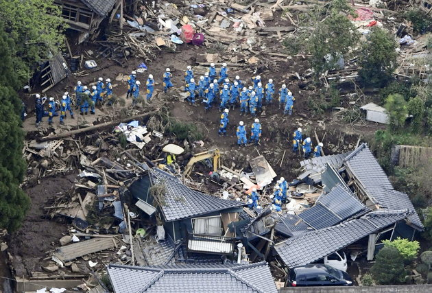 Rescue workers conduct a search and rescue operation to a collapsed house at a landslide site caused by earthquakes in Minamiaso town, Kumamoto prefecture, southern Japan, in this photo taken by Kyodo April 16, 2016. Mandatory credit REUTERS/Kyodo ATTENTION EDITORS - FOR EDITORIAL USE ONLY. NOT FOR SALE FOR MARKETING OR ADVERTISING CAMPAIGNS. THIS IMAGE HAS BEEN SUPPLIED BY A THIRD PARTY. IT IS DISTRIBUTED, EXACTLY AS RECEIVED BY REUTERS, AS A SERVICE TO CLIENTS. MANDATORY CREDIT. JAPAN OUT. NO COMMERCIAL OR EDITORIAL SALES IN JAPAN.