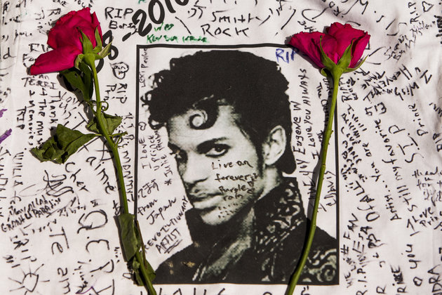 Flowers lay on a T-shirt signed by fans of singer Prince at a makeshift memorial place created outside Apollo Theatre in New York, Friday, April 22, 2016.