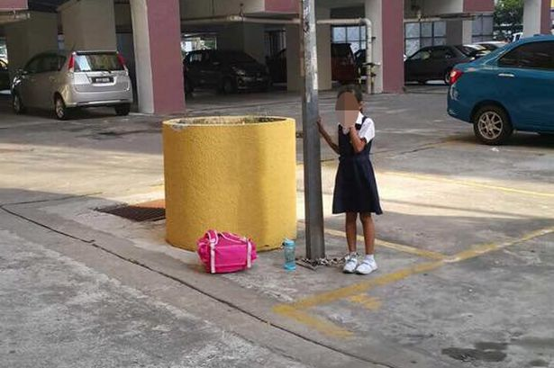 child chained to a pole
